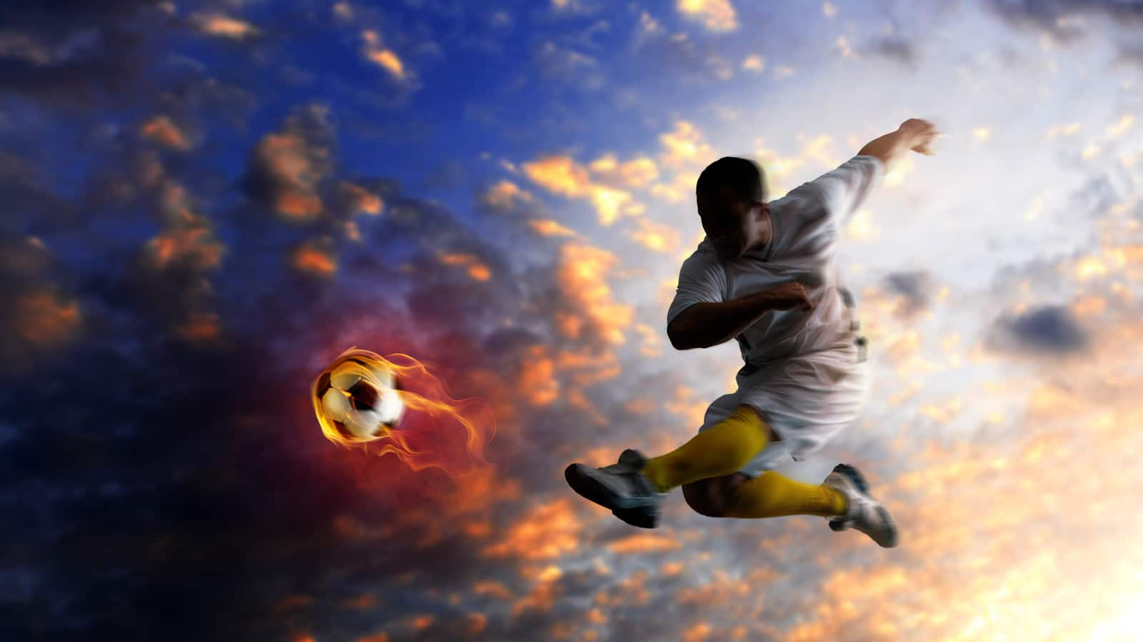 Young soccer player kicking a flaming football