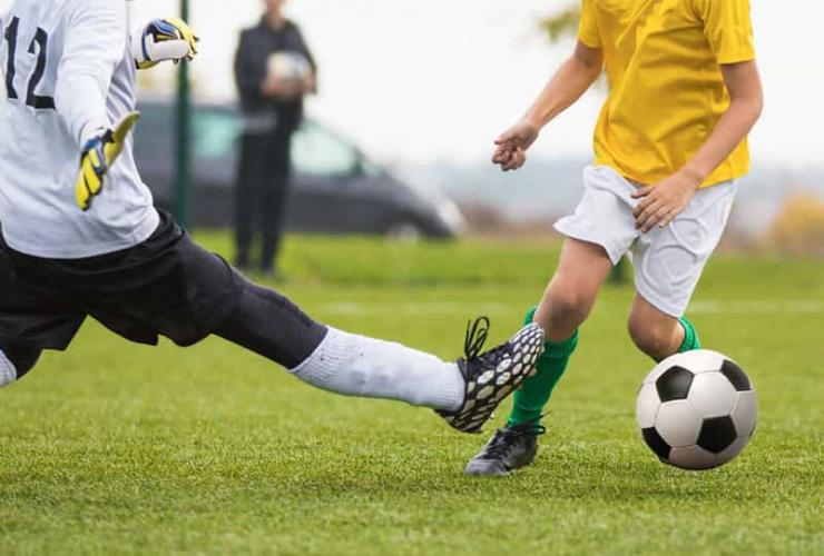 Soccer player dribbling around the goal keeper