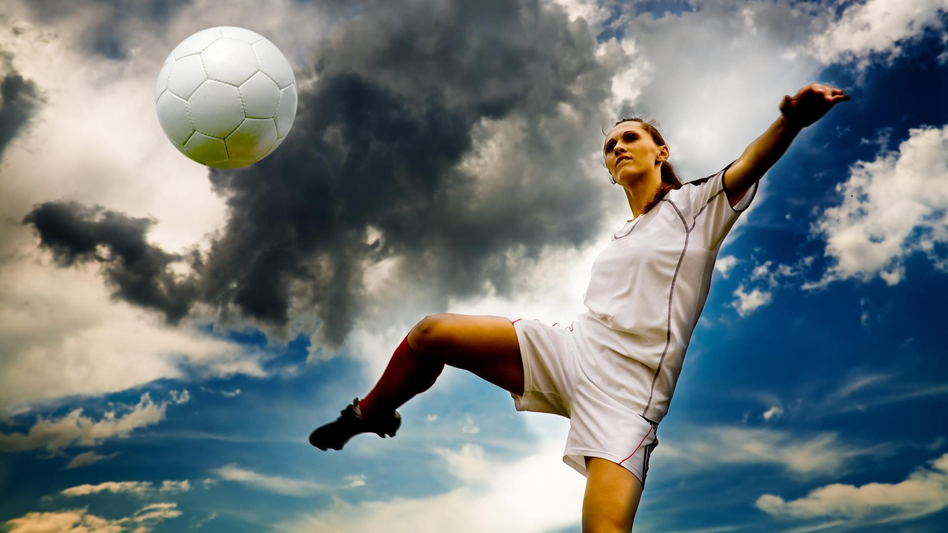 Female soccer player volleying a ball, showing great touch