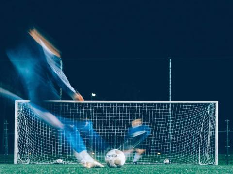 Blurred time lapse image of a striker taking a penalty spot kick