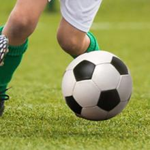 Soccerball being taken around a player