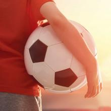 Photo of soccerball under arm
